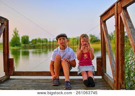 Children Sitting On Pier. Two Children Of Different Age - Elementary Age Boy And Preschool Girl Sitt