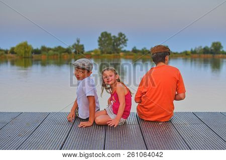 Children Sitting On Pier. Siblings. Three Children Of Different Age - Teenager Boy, Elementary Age B