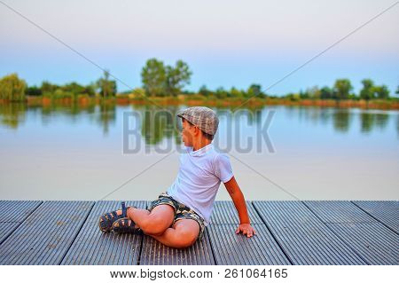 Little Boy Sitting On Pier. Elementary Age Boy Sitting On A Wooden Pier. Summer And Childhood Concep