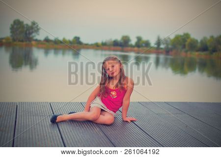 Little Girl Sitting On Pier. Preschool Girl Sitting On A Wooden Pier. Summer And Childhood Concept.