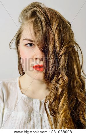 Portrait Of Blonde Young Woman With Curly Hair Closed One Eye, Stock Photo Image