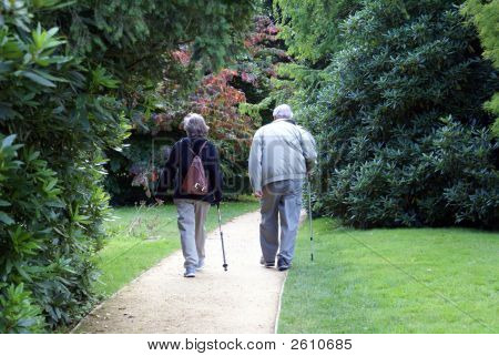 A Couple With Walking Sticks Walking Together