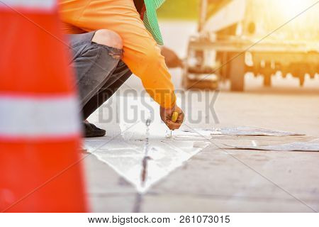 Thermoplastic Spray Marking Machine During Road Construction. Workers Painted White Lines On The Roa
