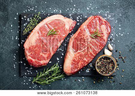 Fresh Raw Prime Black Angus Beef Steaks On Stone Board: Striploin, Rib Eye. Top View. On A Dark Back