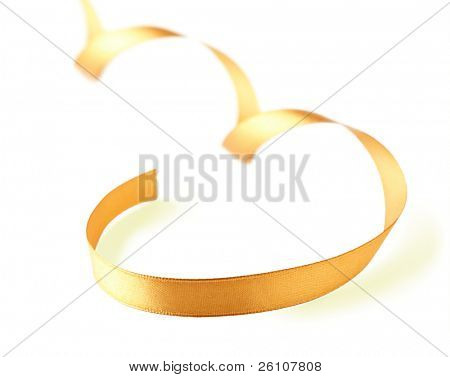 Curved gold silk ribbon isolated on white. Closeup. Celebratory image.