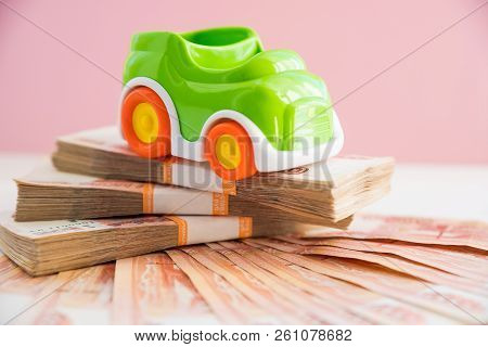 Toy Car Model And Money, Russian Money. Car Expenses Concept.the Model Of The Car On The Background