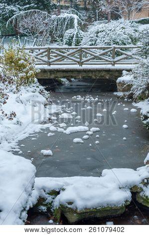 Frozen Stream And Little Bridge Under The Snow In Winter In The Trocadero Gardens In Paris, France