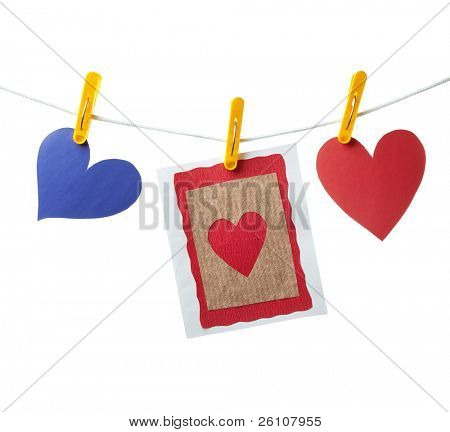 Blank handmade card and two paper hearts hanging on the clothesline. Isolated on white background.