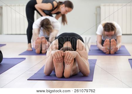 Young Female Yoga Instructor Teaching Seated Forward Bend Exerci