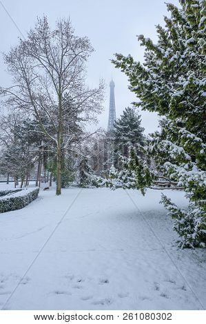 Eiffel Tower Under The Snow Behind Trees From The Trocadero Gardens In Winter In Paris, France