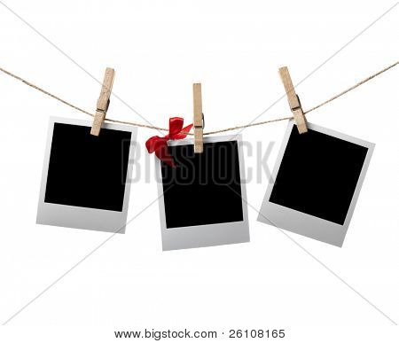 Instant photos with red bow hanging on the clothesline. Isolated on white.