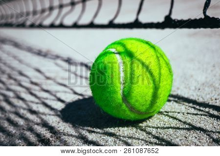 One Green Tennis Ball On Court, Sport Competition Concept. Tennis Net Shadow On The Ball. Macro View