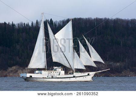 Two-masted Schooner Passes Near The Dark Forest Shore