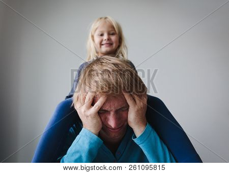 Difficult Parenting- Father Is Tired Having Headache While Daughter Makes Noise