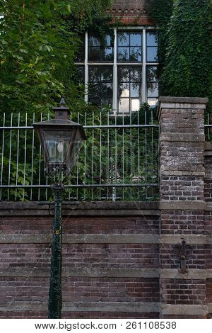 Street Lamppost In Front Of Brick Fence And Big House