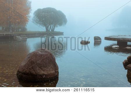 Foggy Autumn Landscape With Orange Tree, Stones In The Water And Mirror Reflection In Lake, Horizont