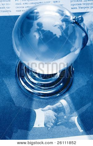 daily handshake under Earth globe on newspaper