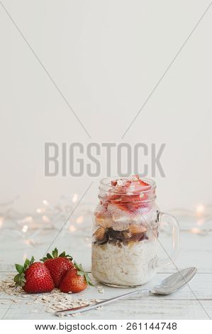 Vertical Photo Of Overnight Oats With Strawberry Served On Wooden Table In A Jar With Spoon. Healthy