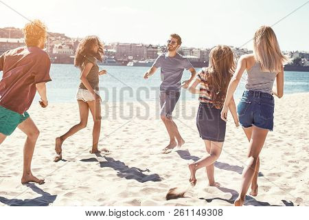 Friends On The Beach. Happy Young Friends Group Have Fun And Celebrate While Jumping And Running On
