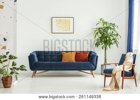 Mid-century Modern Chair With A Blanket And A Large Sofa With Colorful Cushions In A Spacious Living