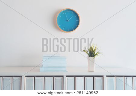 Modern Bright Business Office Interior Detail Depicting Wall Clock And Shelf With Books, Plant And F