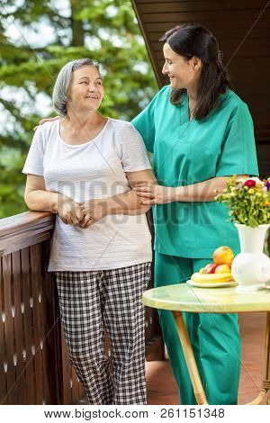 Senior Woman With Her Home Caregiver Spending Time Together. Female Nurse Consoling Senior Woman At