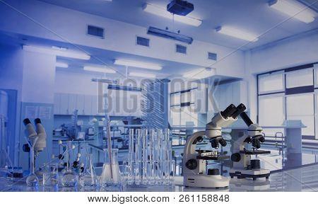 Modern Scientific Laboratory Interior. Laboratory Glassware And Microscope On The Glass Table.