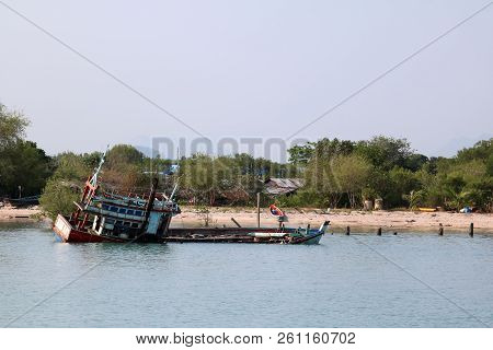 poster of Wreckage wooden fishing boat was being stuck on the beach for long time .