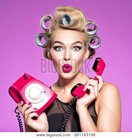 young woman with wonder face holds retro phone. Girl with blue curlers talking by red telephone. Young woman with blue curlers calling by retro phone.