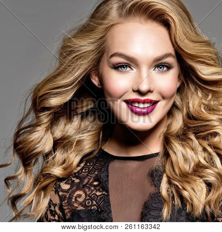 Blond smiling woman with long curly beautiful hair. Makeup. Fashion make-up. Fashionable girl dressed in black dress. Closeup portrait. Gorgeous face of an attractive fashion model. Happy girl.