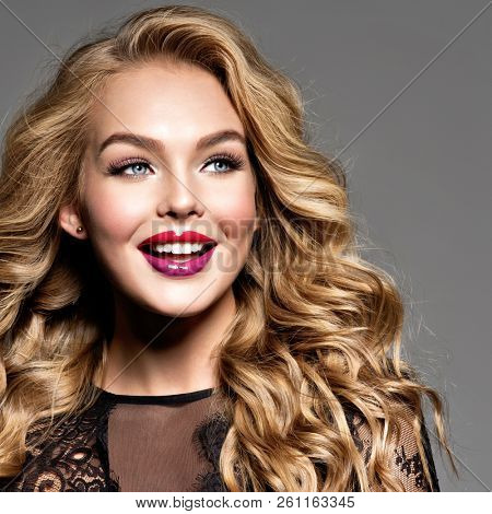 Blond smiling woman with long curly beautiful hair. Makeup. Fashion make-up.  Closeup portrait. Gorgeous face of an attractive fashion model. Bright red lips.  Happy girl. Cheerful caucasian woman