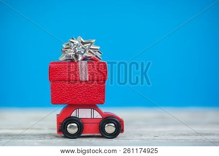 Miniature Red Car Carrying A Christmas Gift Box On Blue Background. Christmas And New Year Concept