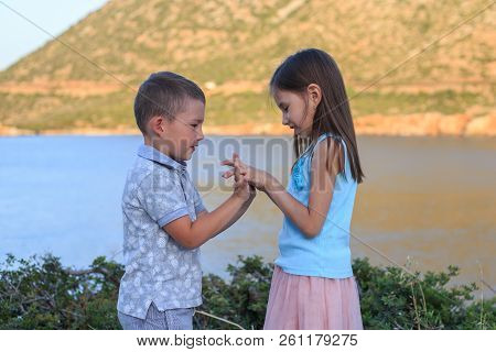 Girl And Boy Together Outdoors. Small Brother Playing With Older Sister.