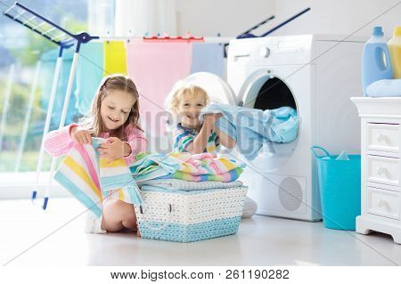 Children In Laundry Room With Washing Machine Or Tumble Dryer. Kids Help With Family Chores. Modern