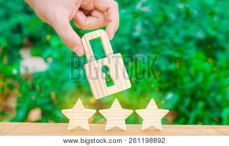 Three Stars And A Hand Holding A Lock. The Concept Of High Quality And Protection. Consolidation Of