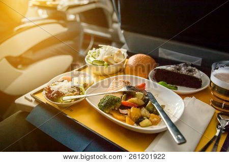 Food Served On Board Of Business Class Airplane On The Table. Young Women Having A Meal On Board Of