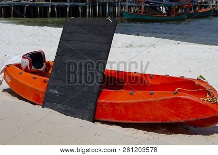Red Kayak And Blank Billboard On Sunny Beach Photo. Black Board Outdoor Mockup. Cafe Or Tourist Serv