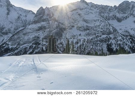 Sunny Winter Day With The Snowy Peaks Of The Alps Mountains, Fir Trees, And A Thick Layer Of Ice And