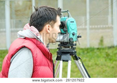 Civil Engineer Land Survey With Tacheometer Or Theodolite Equipment. Worker Checking Construction Si