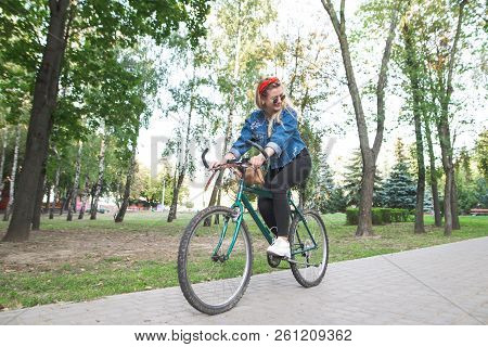 Young Happy Girl In Stylish Clothes Rides A Green Bike In The Park. Student Girl Is Actively Resting