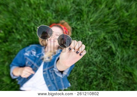 Stylish Girl Lying On A Green Lawn And Holding Sunglasses In Her Hands. Sunglasses In The Hands Of A