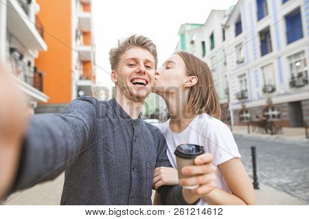 Portrait Of A Lovers Of A Young Couple Takes Selfie On The Street Of The Town. Smiling Young Man Wit
