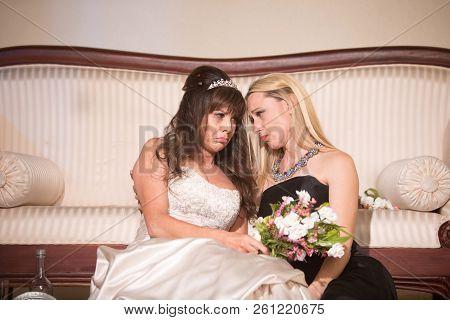 Friend Consoling Sad Bride At A Wedding