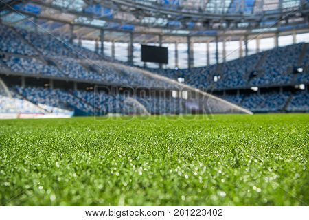 Grass On Stadium In Sunlight. Closeup Of A Green Football Field. Wet Stadium Grass In The Morning Li