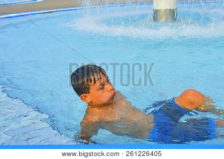 Summertime And Swimming Activities For Happy Children In The Pool. Cute Boy In Water Park. Summer An