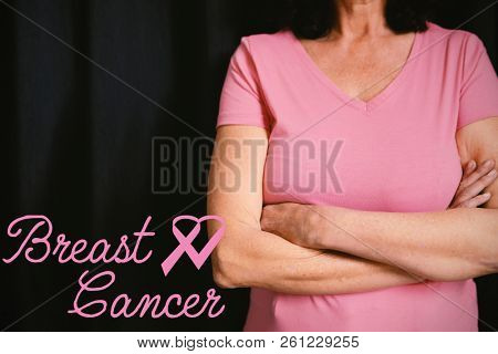 Breast cancer text with ribbon against  women in pink for breast cancer focus on crossed arms