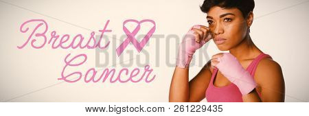Breast cancer text with ribbon against serious looking woman fighting against breast cancer