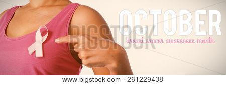 Pink breast cancer awareness text against woman pointing at ribbon for breast cancer awareness