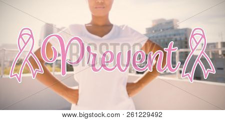 Prevent text with breast cancer awareness ribbon against strong woman standing for breast cancer awareness