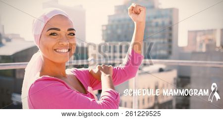 Schedule mammogram text with breast cancer awareness ribbon against strong woman in city with breast cancer awareness